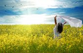 Freedom, young woman with a shawl in rapeseed field