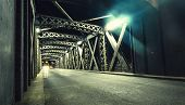 Asphalt Road Under The Steel Construction Of A Bridge In The City. Night Urban Scene With Car Light poster