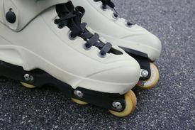 stock photo of inline skating  - pair of white aggressive skates on asphault - JPG