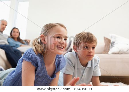 poster of Children playing video games while their parents are watching in a living room