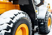 Snow Covered Tractor Wheels. Yellow Wheel Front Loader. Heavy Diesel Tractor, Construction Machinery poster
