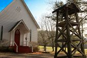 foto of funeral home  - White church in country with big bell in wooden frame - JPG