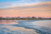 freezing lake after sunset with houses at waterfront - Boyd Lake in northern Colorado poster