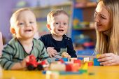 Children Group Playing With Teacher In Day Care Centre Nursery Playroom poster