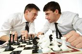 Two men looking at each other aggressively while playing chess
