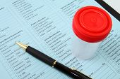 picture of urination  - Urine container and pen on lab test form