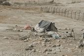 Bedouin Houses In The Desert Near Dead Sea. Poor Regions Of The World. A Indigent Bedouin Sitting At poster