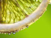 Tropfen Saft fallen der saftige Zitrone. Ein starkes Licht hinter die Zitrone gibt den dunklen Aspekt