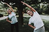 Young Couple In Sportswear Doing Exercises In Park. Sport And Healthcare Concept. Young Man Outdoor. poster