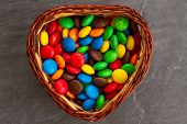 Wicker Candy In The Shape Of A Heart Full Of Bright Multi-colored Sweets Dragee On A Stone Gray Back poster