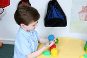 Boy Playing With Colorful Dough At Preschool