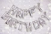 Birthday Party Decoration - Happy Birthday Letters Air Balloons Over White Brick Wall With Lights poster