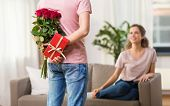 couple, relationships and people concept - happy woman looking at man hiding flowers and gift behind poster