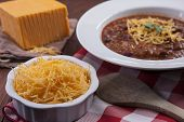 Bowl Of Shredded Cheese And Chili. A Close Up Of A Small Bowl Of Cheddar Heese And A Bowl Of Chili. poster