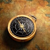 foto of old-fashioned  - An old fashioned brass compass on a Treasure map background - JPG