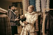 Woman In Fur Coat With Dog And Man In Shop. Purchase And Fashion Concept. Couple In Love: Girl With  poster