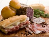 focaccia com salame presunto e queijo sobre placa de corte