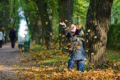 Mädchen und Blätter im Herbst