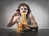 Man eating pasta and drinking red wine