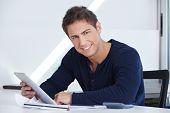 Glücklich Designer sitzt an seinem Schreibtisch mit einem Tablet-PC in der hand