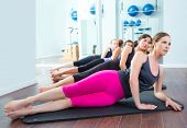 Grupo de mulheres de Pilates deitado na esteira, com instrutor de ginástica na frente