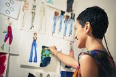picture of tailoring  - Young people and small business hispanic woman at work as fashion designer and tailor looking at sketches of new collection in atelier - JPG