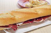primer plano de un sándwich de jamón serrano español y tapa de tortilla de patatas