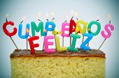 letter-shaped candles of different colors forming sentence cumpleanos feliz, happy birthday in spani