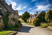 stock photo of creeper  - Ancient cotswold stone houses and flower garden in Cotswolds village of Icomb - JPG