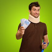Young Man Wearing Cervical Collar Holding Euro Note Isolated On Green Background
