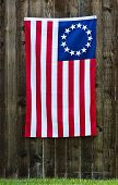 stock photo of betsy ross  - 13 Star American flag the Betsy Ross flag displayed on rustic wooden fence - JPG