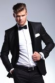 portrait of an elegant young fashion man in tuxedo holding a hand in his pocket and the other on his