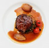 Tenderloin steak in plate, isolated on black background