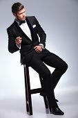 elegant young fashion man in tuxedo sitting on a chair and smoking while looking away from the camer