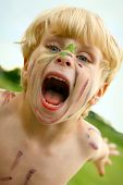 pic of growl  - A litle boy growls at the camera with a painted face outside - JPG