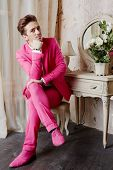 Young man in pink suit and shoes sits on chair with crossed legs and propping chin with his hand
