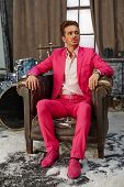 Young man in pink suit sits in scuffed old armchair in room powdered with snow, drum-set is behind h