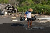 Traditional Sea Salt Production On On The Volcanic Black Sand, Bali, Indonesia