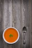 A bowl of tomato soup with a tarnished silver spoon, against a rustic wood tabletop. Vintage style with intentional vignette and selective desaturation and space for your text