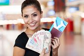 beautiful young woman holding passport, air ticket and cash at airport