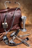 Old doctor's bag and collection of antique medical instruments such as stethoscope, reflex hammer and head mirror