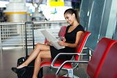 smiling young businesswoman reading newspaper while waiting for her flight