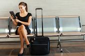 stock photo of sitting a bench  - beautiful young woman using tablet computer at airport - JPG