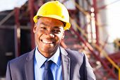 smiling african engineer at industrial site