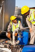 two petrochemical workers inspecting pressure valves on a fuel tank