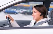 beautiful woman driver is safely talking phone in a car using a headset