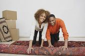 Young couple rolling rug