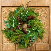 stock photo of carving  - A green Christmas wreath with pine cones and berries hangs on an ornately carved wooden door. 