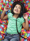 Cute little girl listening music through headphones while lying on beanbag