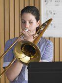 Garota do colegial tocando trombone na aula de música